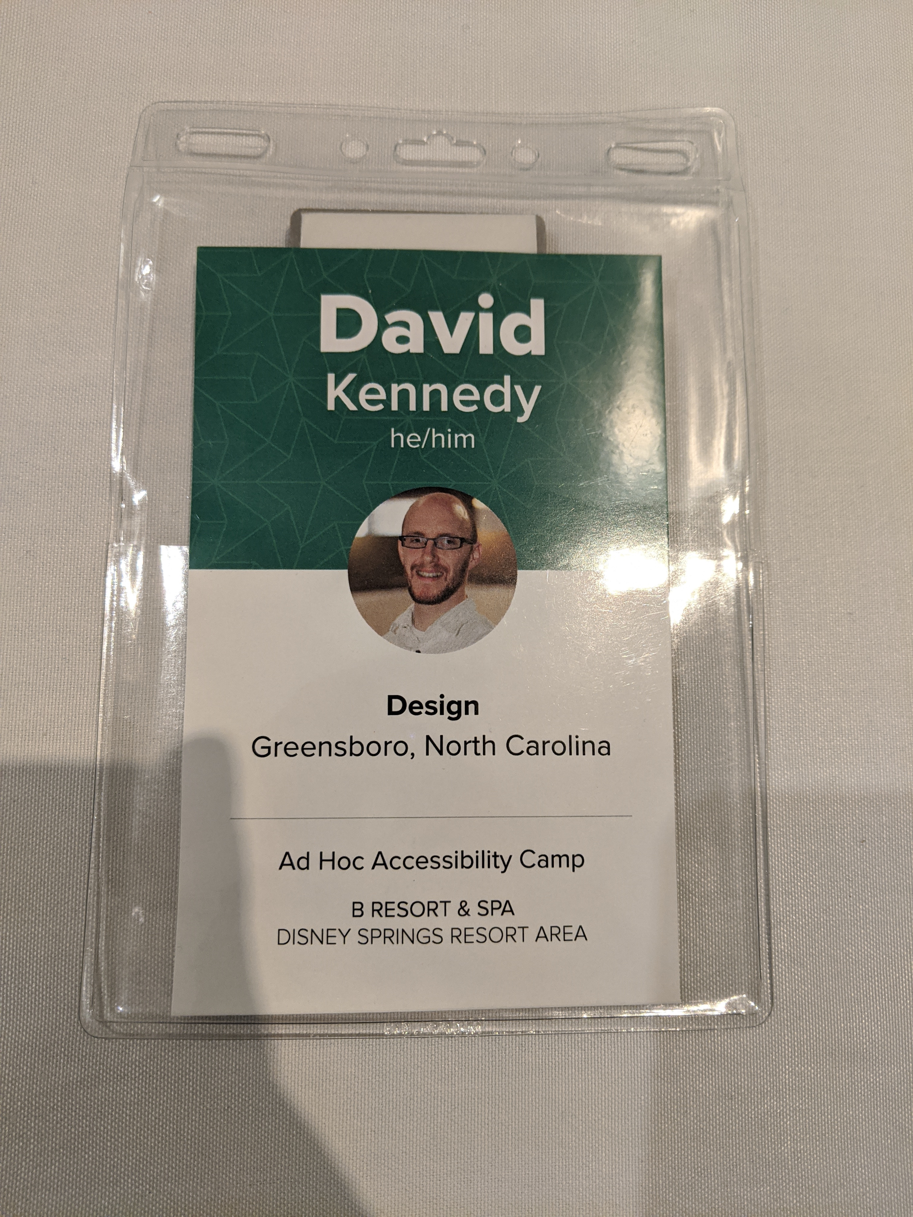 Ad Hoc Accessibility Camp 2020 conference badge with green and white colors and David Kennedy, design on front.