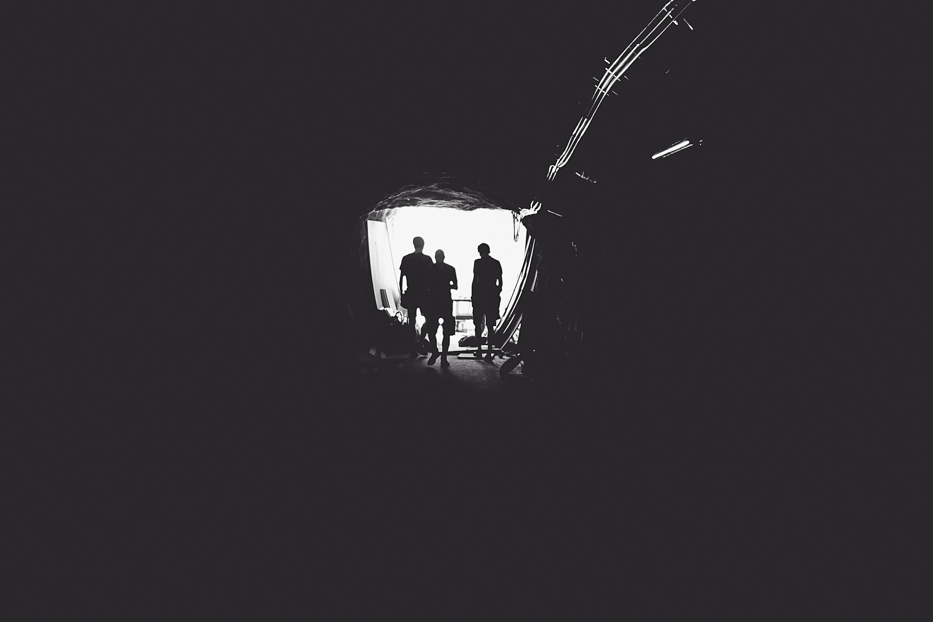 Tunnel showing light and three people at the end.